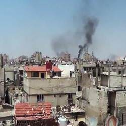 picture of damascus homes and black smoke rising from bombs